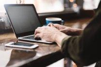 Homme travaillant sur ordinateur portable au café — Photo de stock
