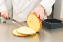 Cropped image of Baker slicing cake — Stock Photo