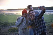 Three young adults taking smartphone selfie at seaside sunset — Stock Photo