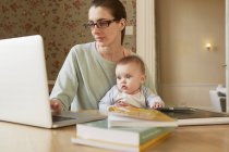 Bambina seduta sulle ginocchia della madre a fissare il computer portatile — Foto stock