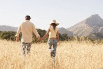 Rear view of couple strolling in field of long grass, Majorca, Spain — Stock Photo