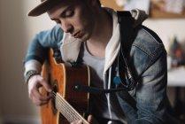 Giovane a casa, a suonare la chitarra — Foto stock