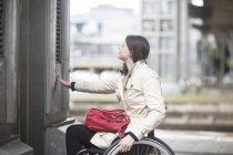Giovane donna che utilizza sedia a rotelle premendo controllo per ascensore urbano — Foto stock