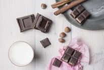 Top view of chocolate cubes, hazelnuts, cinnamon sticks, glass of milk on table — Stock Photo