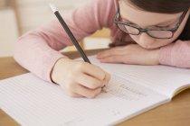Крупним планом дівчина виконує домашнє завдання в таблиці — стокове фото