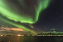 Auroras boreales cielo iluminado por encima del puerto de Tromso - foto de stock