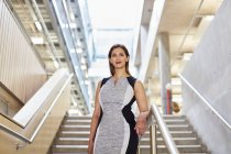 Portrait of businesswoman standing on office stairway — Stock Photo