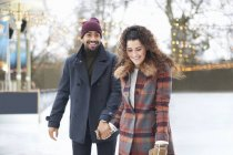 Couple on ice rink holding hands smiling — Stock Photo