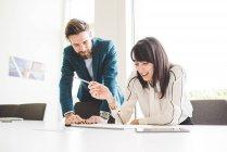 Молодой бизнесмен и женщина пишут на блокноте за столом переговоров — стоковое фото