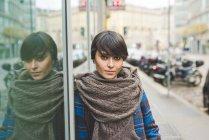 Porträt einer jungen Frau, die sich gegen Fenster lehnt, im Freien — Stockfoto