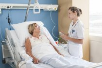 Infirmière s'occupant au patient dans le lit d'hôpital — Photo de stock