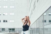 Mujer joven con las manos en la cabeza fuera del edificio de oficinas - foto de stock