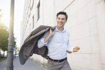Empresario corriendo en la calle llevando traje chaqueta y baguette - foto de stock
