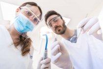 Point de vue du patient du dentiste et de l'infirmière dentaire tenant de l'équipement dentaire — Photo de stock
