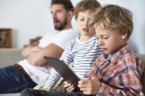 Boys with father using digital tablet — Stock Photo