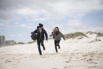 Pareja joven corriendo en la playa barrida por el viento, Cabo Occidental, Sudáfrica - foto de stock