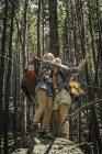Adolescente y joven excursionista mujer abrazando en roca en el bosque, Red Lodge, Montana, Usa - foto de stock