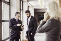 Businesswomen reading smartphone update in office corridor — Stock Photo