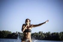 Mujer sosteniendo la nariz, saltando en el agua, Berlín, Alemania - foto de stock
