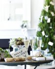 Table of champagne with xmas crackers and gifts — Stock Photo