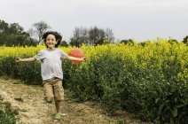 Boy running on yellow flower field track pulling red balloon — Stock Photo