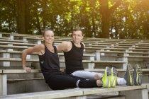 Hombre y mujer jóvenes entrenando, haciendo flexiones en la escalera del estadio - foto de stock