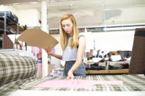 Young woman working in leather jacket manufacturers — Stock Photo