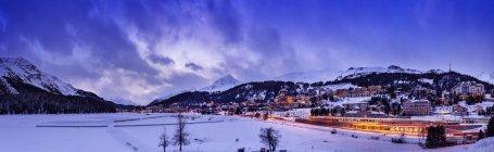 Villaggio sotto la montagna il paesaggio coperto di neve illuminato la sera, Sankt Moritz, Svizzera — Foto stock