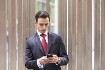 Businessman in city looking at smartphone — Stock Photo