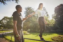 Woman holding hands with  personal trainer walking on park fence — Stock Photo