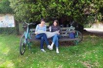 Молодих дорослих сестри з велосипедами, сидячи на лавці, дивлячись на карту — стокове фото