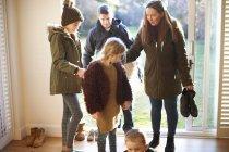 Famille arrivant à la maison ensemble par temps froid — Photo de stock
