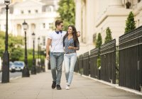 Young couple strolling on city street, London, UK — Stock Photo