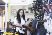 Woman in bicycle shop holding paperwork — Stock Photo