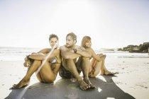 Trois milieu adultes amis portant des maillots de bain assis sur la plage, le Cap, Afrique du Sud — Photo de stock