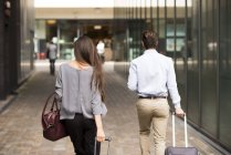 Rear view of young businessman and woman with wheeled suitcases, London, UK — Stock Photo