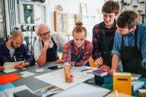 Senior homme artisan brainstorming idées avec un groupe de jeunes hommes et femmes dans l'atelier des arts du livre — Photo de stock
