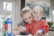 Mother and son doing painting together — Stock Photo