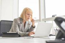 Зрелая деловая женщина читает новости на офисном ноутбуке — стоковое фото