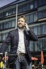 Homme d'affaires avec vélo faisant appel smartphone en ville — Photo de stock
