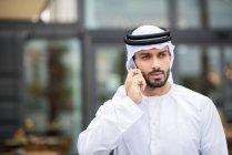 Hombre usando dishdasha caminando por la calle hablando por teléfono inteligente, Dubai, Emiratos Árabes Unidos - foto de stock