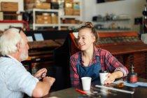 Молода Майстриня п'є каву, базікати і сміятися з старшим майстром в книжковому мистецтві семінар — стокове фото