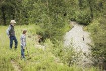 Людина і хлопчика, що тримається вудок дивиться людина риболовля на річці — стокове фото