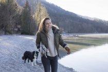 Cane da passeggio donna sul lungolago nelle Alpi bavaresi — Foto stock