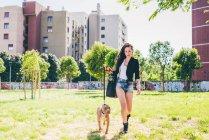Jeune femme marche pit bull terrier dans le parc urbain — Photo de stock