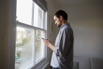 Hombre adulto medio en la ventana de la sala de estar leyendo textos de teléfonos inteligentes - foto de stock