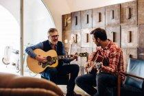 Hijo de padre y adulto tocando la guitarra en la sala de estar - foto de stock
