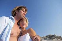Пара влюбленных, обнимающихся на пляже, голубое небо — стоковое фото