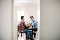 Male couple at home, sitting at table, laughing — Stock Photo