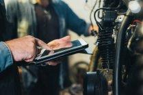 Два зрелых мужчины, работающие в гараже, используя цифровые планшеты, крупным планом — стоковое фото